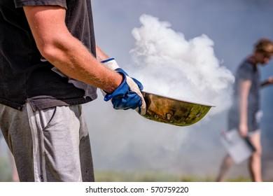 Man brings spewing smoke dish.