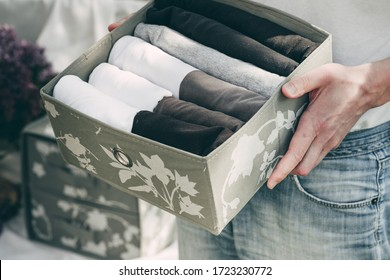 Man  brings wardrobe order puts everything on its place hides things in boxes. Closet organized. Capsule wardrobe. Spring cleaning.