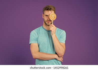 Man with bristle likes lollipop. Cheat meal concept. Sugar harmful for health. Guy hold lollipop candy violet background. Taste of childhood. Lollipop fun. Man eat big colorful sweet lollipop.