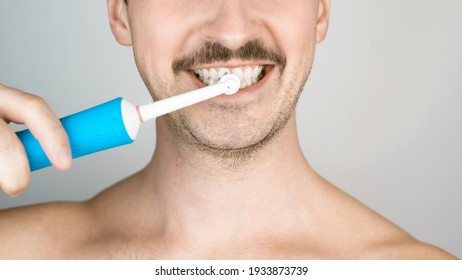 Man with bristles brushing teeth, daily hygiene procedure. Close-up portrait of man with modern electric toothbrush. Oral health