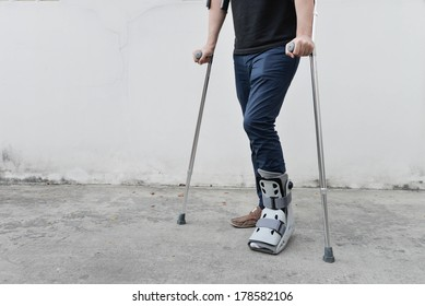 man with broken ankle wearing ankle support with walking crutches