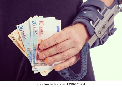 man with broken arm and euro notes
