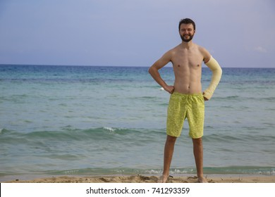 A man with broken arm is on a beach