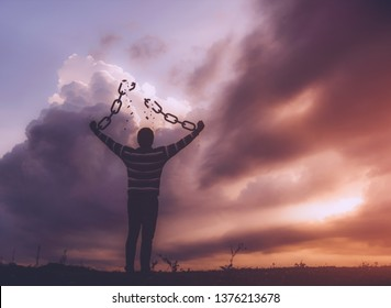 Man with broken chains at the time of the sunrise . concept of freedom
