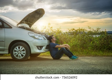Man with broken down car flat tire in the middle of the street