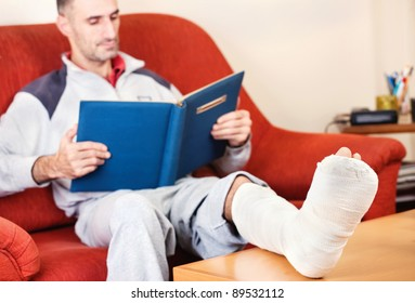 man with a broken leg on a sofa at home  reading book; focus on cast