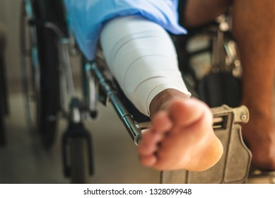 Man with a broken leg sits in a wheelchair in hospital room,copy space.