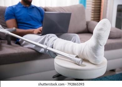 Man With Broken Leg Sitting On Sofa Using Laptop