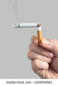 Man with a broken lit cigarette in his hand, symbolizing quitting smoking