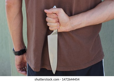 a man in brown clothes holds a gray knife behind his back