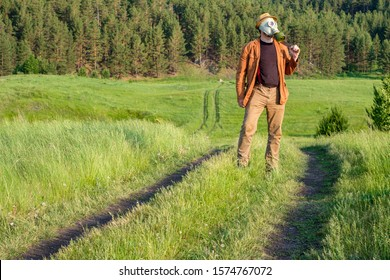 a man in brown clothes stands proudly on a green field on his shoulder a sword on his face a gas mask on his head a hat. background forest and field