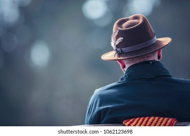 Man in brown fedora hat sitting outdoor on bench. Rear view.