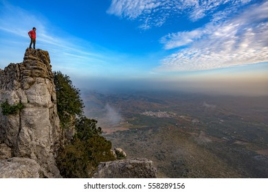 Man with brown hat and in red jacket stands on top of a rock in El Torcal de Antequera, Spain, overlooking the valley below.