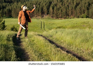 a man in a brown jacket and jeans stands in the field in his hand a sword on his head a hat and a gas mask takes a selfie. robber in role-playing game absolves himself themselves