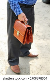 Man with brown leather bag in hand on road. Cropped view.