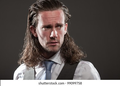 Man brown long hair with expressive face wearing grey suit and blue tie. Angry looking. Aggressive. Isolated on grey background.