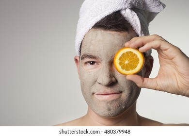 man with a brown mud mask on this face and orange, copy space