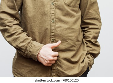 Man in brown shirt shows thumb up isolated on the white background. Success concept. Selective focus and shallow DOF