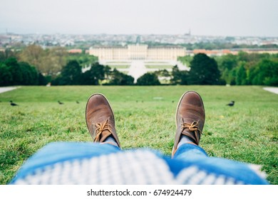 A man with a brown shoes lays on the green grass hill in the back of schonbrunn palace, Vienna, Austria.