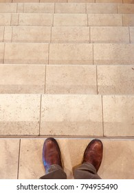 A man in brown shoes and brown pants stepping over a marble-tiled stair.