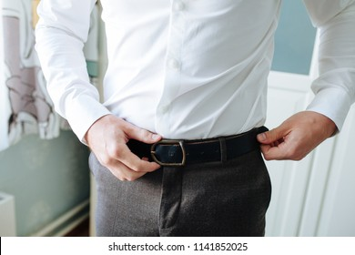 The man in brown trousers and a white shirt fastened a black leather trouser belt. Men's formal outfit. Fashion.