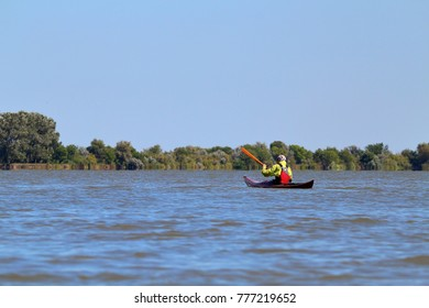 Man in brown wooden handmade kayak paddling at river on biosphere reserve in spring. Kayaking in Danube river