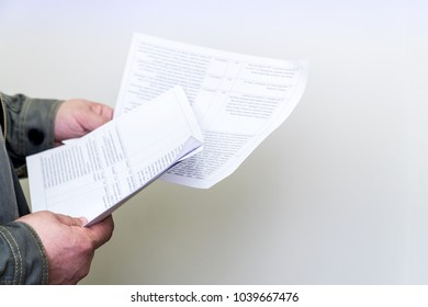 Man browsing business papers and documents on white background