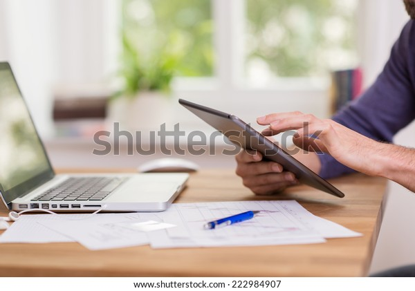 Man browsing the internet on a tablet using his finger to navigate the touchscreen as he sits working at his desk at the office