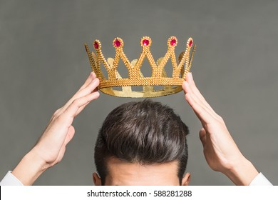 Man brunette holding above his head a golden crown on a gray background