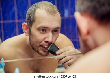 Man brunette shaves his beard in the mirror