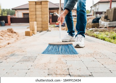 A man with a brush sweeps the paving slabs on the path near the house - general cleaning of the personal plot