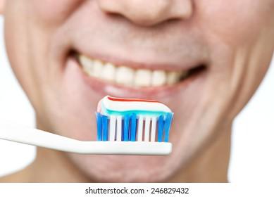 Man brushing teeth toothbrush with toothpaste macro closeup