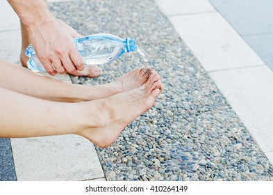 A man is brushing up and washing woman's feet by pouring water from plastic bottle while a hot summer day. Woman's feet are stretched above the stone promenade