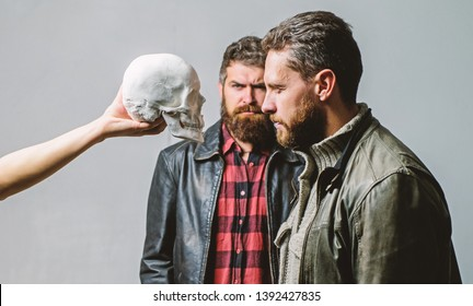 Man brutal bearded hipster looking at skull symbol of death. Overcome your fears. Be brave. Focused on breaking fear. Psychology concept. Human fears and courage. Looking deep into eyes of your fear.
