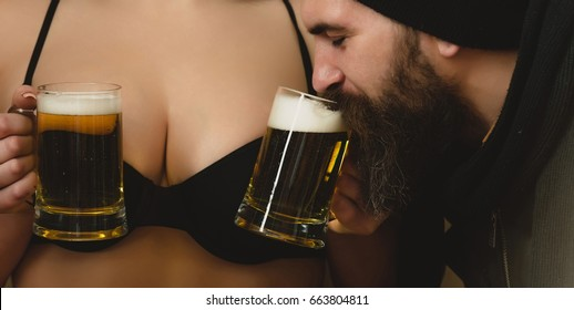 man or brutal hipster with long beard and moustache drinking beer from glass mugs in waitress hands on sexy female breast or bust in black bra background. Alcohol, bad habits and addictive