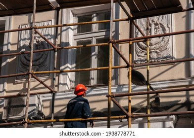 Man builder in orange construction helmet working from scaffolding to renovate historic building wall with ornate sculptural relievo details. Historic building restoration in progress - Shutterstock ID 1938778771