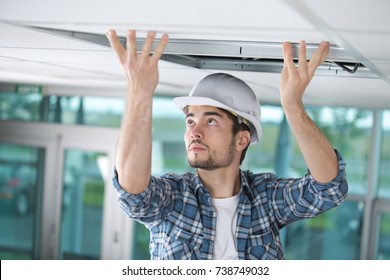 man in builder uniform hand up installing suspended ceiling