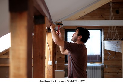 Man building a house and workimg with hammer and wood.