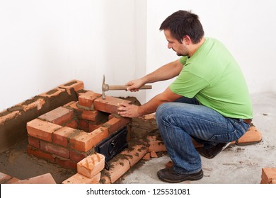Man building masonry heater or fireplace - fitting the next brick