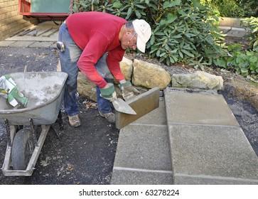 Man building patio steps using concrete pavers