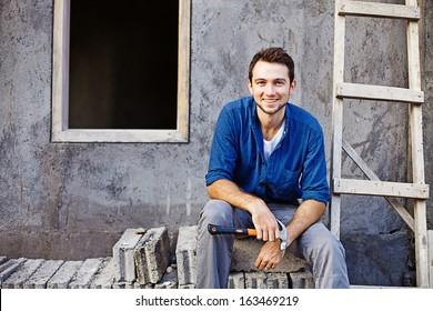 man building or repairing his house
