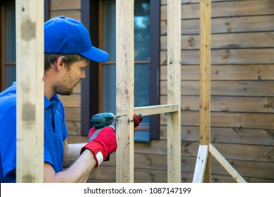 man is building a shed in backyard