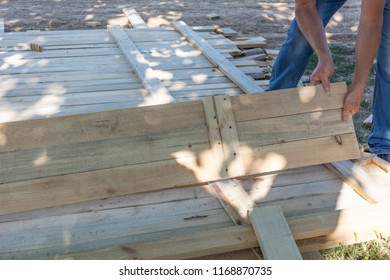 Man building a wooden fence. Workers pick up wooden boards for the fence formwork. Wooden formworks for concrete at construction site.