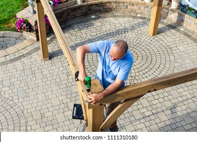 Man building a wooden gazebo on a brick patio with ornamental paving viewed from above as he stands on a ladder screwing together beams