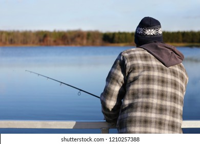 A man is bundled up in warm clothes while fishing off a dock on a small man made lake in the Midwestern United States on a cold day.