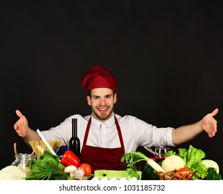 Man in burgundy hat and apron points at food. Cook sits in kitchen near table with vegetables and tools. Vegetarian meal concept. Chef with cheerful face on black background.