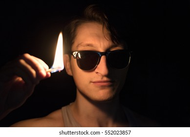 Man with a burning match in the dark. Looking into camera.