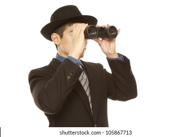A man in business attire and hat using binoculars