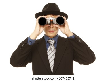 A man in business attire and hat using binoculars (on white)