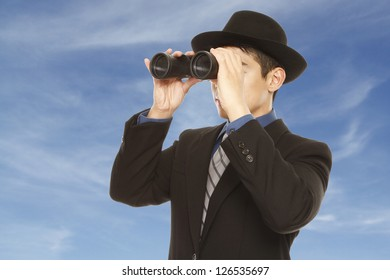 A man in business attire and hat using binoculars (against a dramatic sky background)
